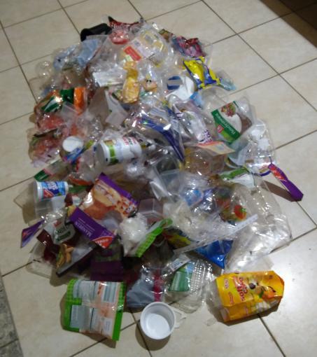 Plastikmüllberg auf einem Fliesenboden. Leere Joghurtbecher, Tüten, in denen Rosinen, Mandeln, Kekse, Gemüse, Käse und vieles mehr waren.